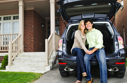 Couple sitting on the trunk of a car parked in front of home